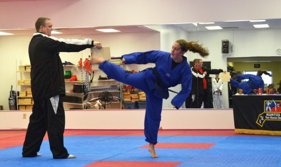 Photo of Hannah breaking board with a kick during Tae Kwan Do test.